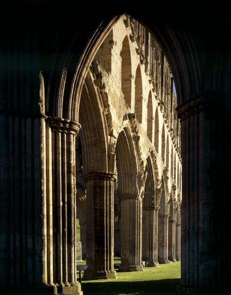 RIEVAULX ABBEY, North Yorkshire. View through silhouetted arch to Presbytery arcade looking North East