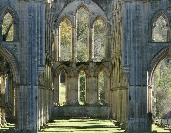 RIEVAULX ABBEY, North Yorkshire. The window at the east end of the abbey church showing autumn colour on the trees beyond