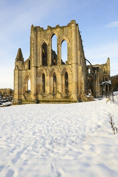 RIEVAULX ABBEY, North Yorkshire. Footprints in the snow lead the way towards the church and presbytery