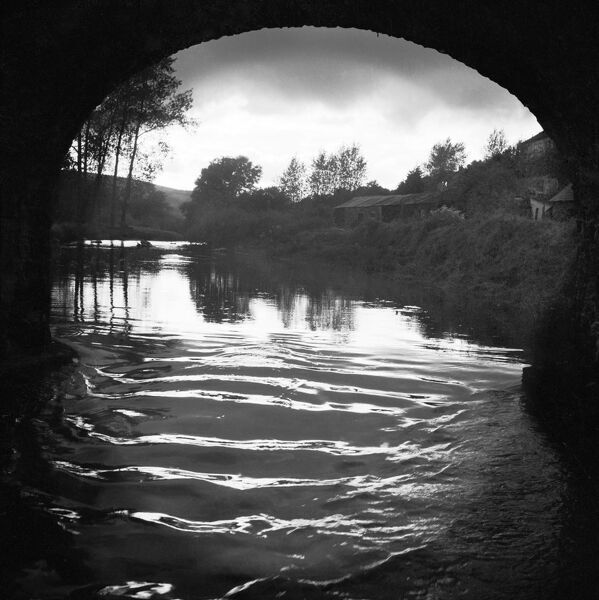 WITHYPOOL, Exmoor, Somerset. A view from beneath the soffit of a stone bridge on the River Barle, looking along a calm stretch of river towards trees, low farm buildings and hills in the distance. Photographed by John Gay in 1956
