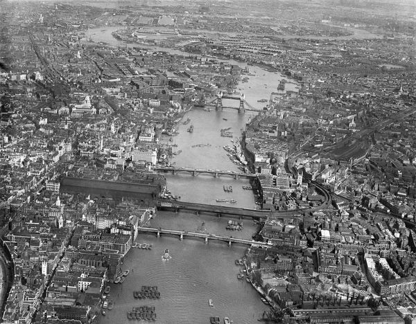 RIVER THAMES, London. An aerial view of central London showing London Bridge, Tower Bridge and the surrounding city landscape. Pre-war, probably mid-1930s. Aerofilms Collection (see Links)