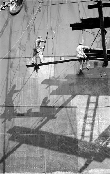 ROYAL ALBERT DOCK, Canning Town, London. Two workmen repainting a ship in dry dock (mid-20th century). The dock was the largest of the three royal docks and opened in 1880. S W Rawlings