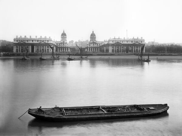 ROYAL NAVAL COLLEGE, Greenwich, London. A view of the Royal Naval College from the opposite bank of the Thames with a moored barge in the foreground. The College moved to this location from Portsmouth in 1873. Photographed by Newton and Co. Date range: c
