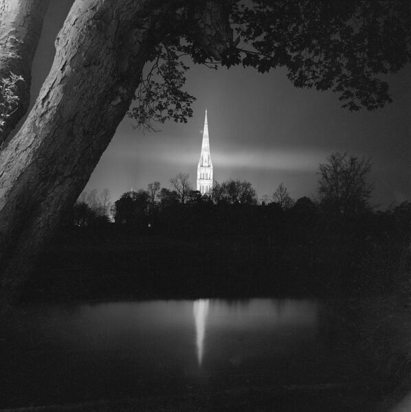 Salisbury Cathedral, Wiltshire. A view of the spire of the Cathedral Church of St Mary illuminated against the night sky by floodlights, and reflected on the surface of the River Avon to its west or south. Photographed by John Gay 1958