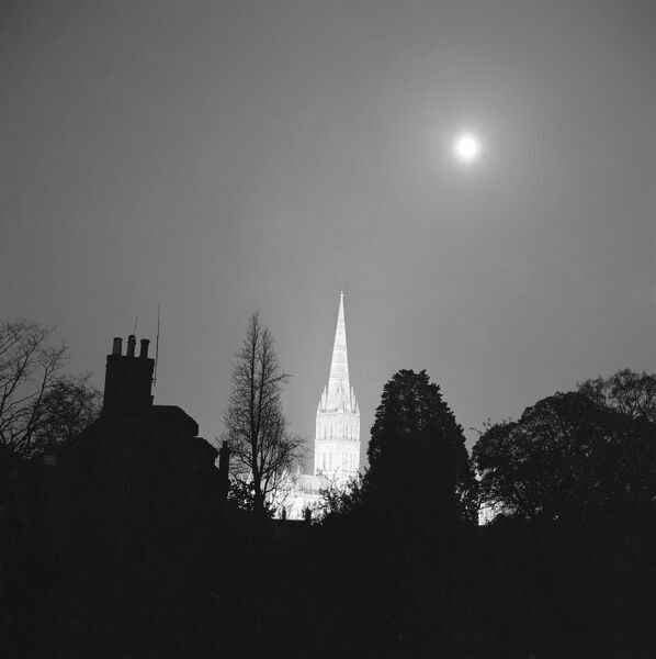 SALISBURY CATHEDRAL, Wiltshire. The Cathedral Church of St Mary towering over silhouetted buildings and trees, and illuminated against the night sky by floodlights. Photographed by John Gay, March-June 1958