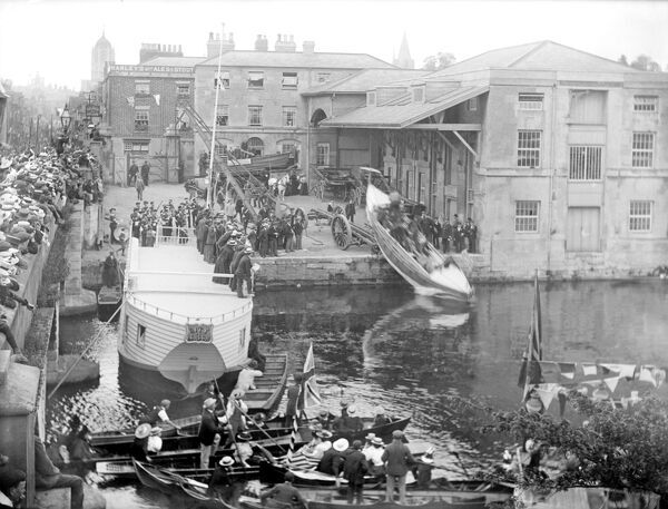 SALTERS YARD, Oxford, Oxfordshire. Looking across the Thames at Folly Bridge toward the Salter Brothers boatyard, established in 1858, with a large number of people gathered to watch the launching of a lifeboat into the river