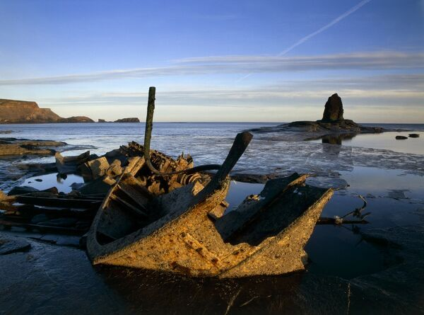SALTWICK BAY, North Yorkshire. View of a shipwreck and Black Nab Rock on the sea shore. The wreck is of the Admiral van Tromp, a fishing vessel wrecked in 1976