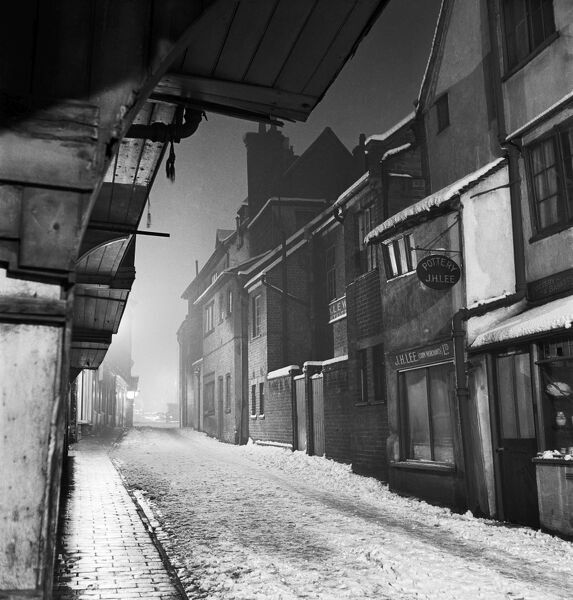 FRENCH ROW, St Albans, Hertfordshire. A snowy evening in French Row, showing first floor jetties of buildings to the left and small shops to the right. Photographed by John Gay. Date range: 1955-1965