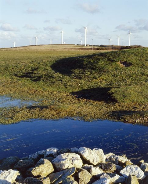 ST BREOCK WIND FARM, St Breock Downs, Cornwall. View looking towards the wind turbines with pond and rocks in the foreground