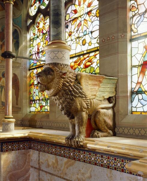 ST MARY'S CHURCH, Studley Royal, North Yorkshire. Interior view of the Winged Lion of Judah in the sanctuary supports one of the double tracery shafts in front of stained glass window