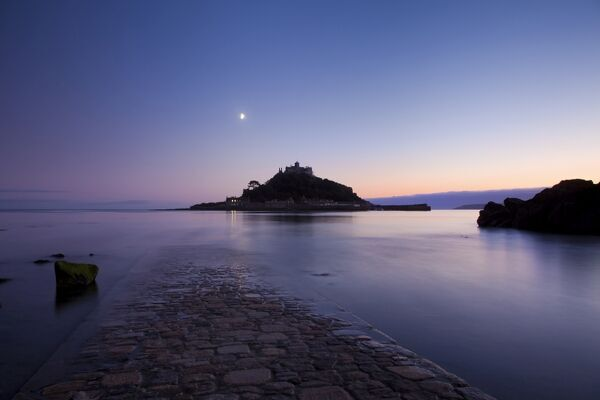 ST MICHAELS MOUNT, Marazion, Cornwall. View along the causeway at dawn, with the moon above the island