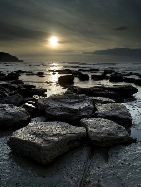 STAITHES, North Yorkshire. View of rocks on the beach at low tide and with a low sun visible through dense cloud