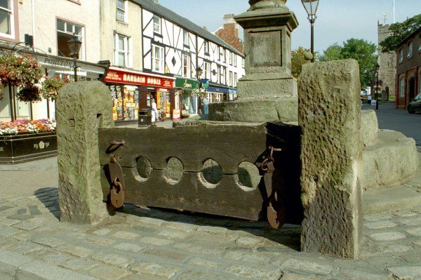 Pair of stone pillars housing wooden stock beams with 2 pairs of leg-holes. Poulton-le-Fylde, Lancashire. IoE 184785
