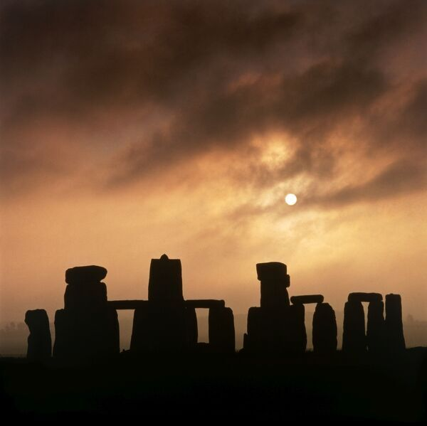 STONEHENGE, Wiltshire. General view of the stones silhouetted against an early morning sky