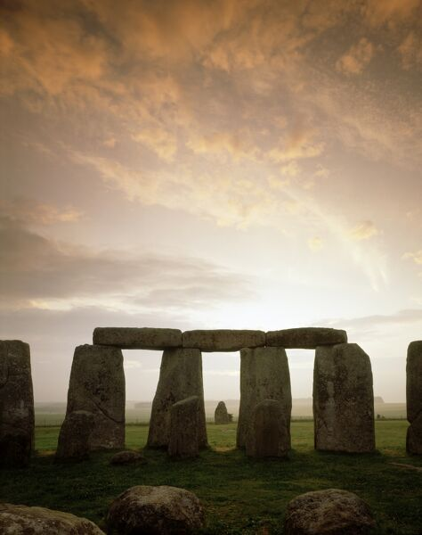 STONEHENGE, Wiltshire. Midsummer sunrise. The Sarsen Circle and Heel Stone in the distance