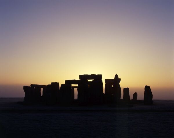 STONEHENGE, Wiltshire. Silhouette of the stones from the North West at sunrise