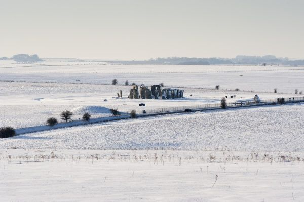 STONEHENGE, Wiltshire. Distant view of the stones in a landscape covered with snow
