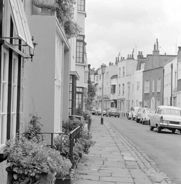 A street with a row of different sized terraced houses and cars parked, possibly in Chelsea, London. John Gay, 1972