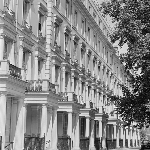 A terrace of four-storey houses decorated in the neo-classical style, including projecting porches with columns and balconies above them, probably in Kensington, trees overhanging from the right and a church at the end of the row