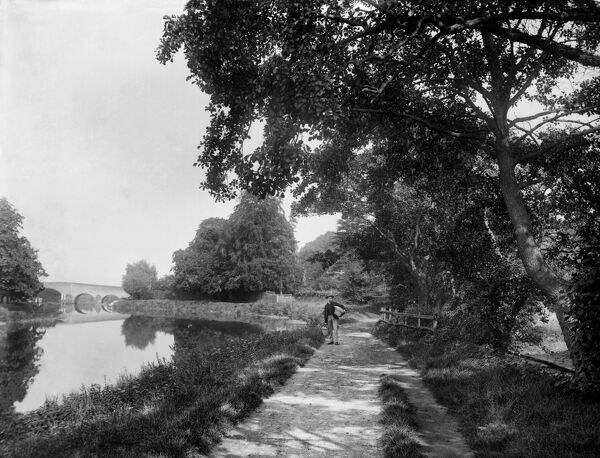 RIVER THAMES near Sonning, Berkshire. A man carrying a couple of baskets stands on the tow path below the lock with the eighteenth century bridge in the distance. Photographed in 1885 by Henry Taunt
