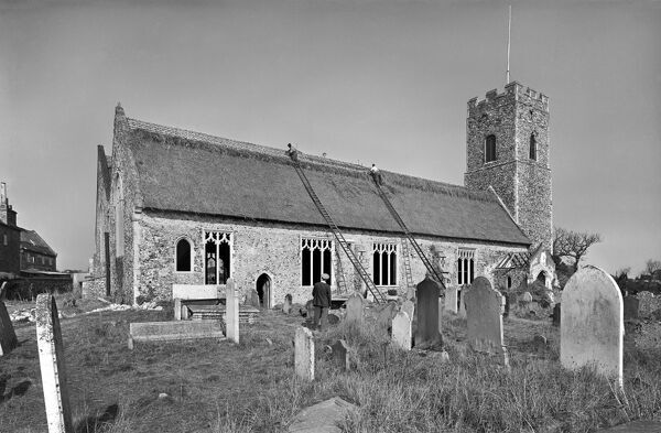 Lowestoft, Suffolk. Thatchers at work on the roof of St Margaret and All Saints Church view from the south east. Photographed by Hallam Ashley in October 1949