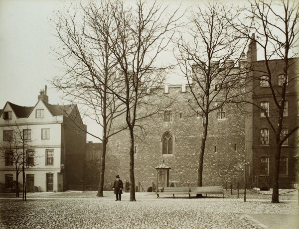 TOWER OF LONDON. Exterior of Beauchamp Tower viewed from Tower Green with a warden on the Green. Anthony Salvin's restoration of this tower starting in 1851 was at that time considered exemplary work. Photographed in 1886 by Bedford Lemere