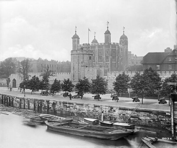 TOWER OF LONDON. View of the Lanthorn Tower and White Tower, with cannon arrayed along the river bank. Photographed in 1890 by Bedford Lemere