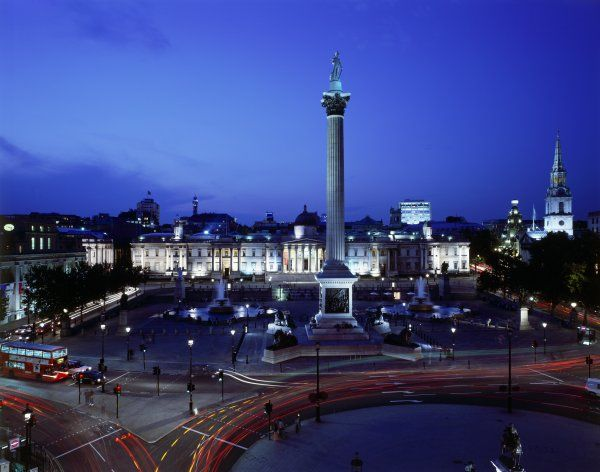 TRAFALGAR SQUARE, City of Westminster, London. Elevated view of the square showing Nelson's Column & National Gallery at night