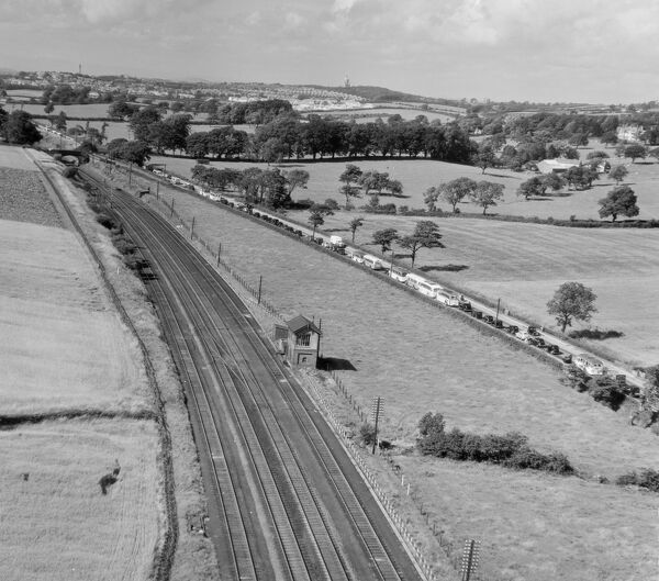 Preston-Lancaster Road, Lancashire. A traffic jam of cars and coaches, on the road, while the adjacent railway lines are empty. Aerial view by Aeropictorial. Aerofilms Collection. July 1951