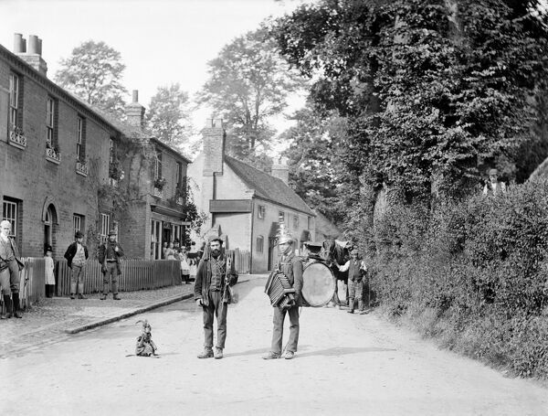 TAPLOW, Buckinghamshire. Looking down a street in the village with two travelling punchinellos or performers, one with a monkey companion and the other a 'one man band'. Photographed by Henry Taunt in 1885