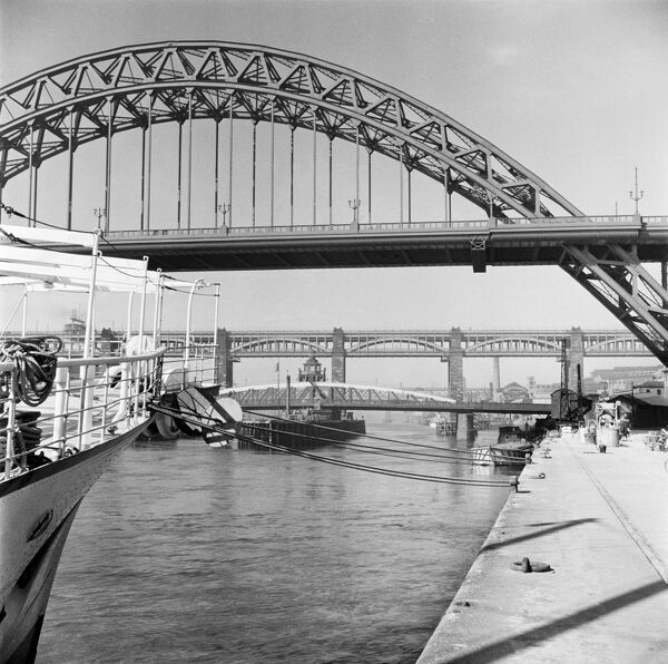 THE TYNE BRIDGES, Newcastle upon Tyne. A view from Newcastle quayside of the Tyne Bridge opened in 1928 by King George V. In the distance the Swing Bridge designed by William Armstrong and the High Level Bridge designed by Robert Stephenson can be seen