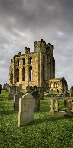 TYNEMOUTH PRIORY, Tyne and Wear. The presbytery and chapel against a grey sky with grave stones in the foreground