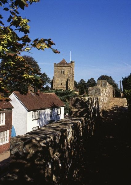BATTLE ABBEY, East Sussex. View looking along the precinct wall towards St Mary's Parish Church