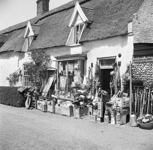 Ludham, Norfolk. Hardware shop with goods on display. Village shops had a reputation for selling everything, and the stock here has spilled out onto the pavement. Photographed by Hallam Ashley June 1953