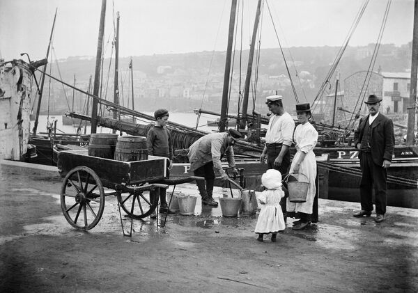 NEWLYN HARBOUR, Cornwall. The coastguard and others collect water in pails from a water carrier on Newlyn harbour. Fishing boats are moored behind them. Photographed in 1907 by S W A Newton for Alfred Newton and Son