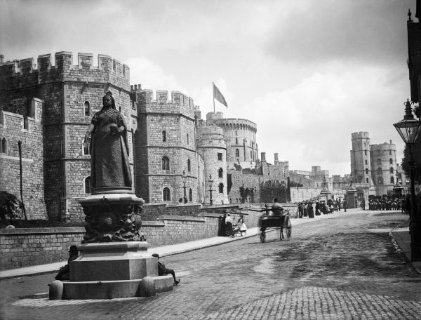WINDSOR CASTLE, Berkshire. View from the junction of High Street and Peascod Street looking along Castle Hill with the statue of Queen Victoria in the foreground