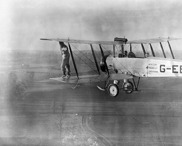 Wing walking without a harness on an Aviation Tours Ltd Avro 504K. Photographed in April 1932. Some damage on negative - produced from copy negative. Aerofilms Collection (see Links)