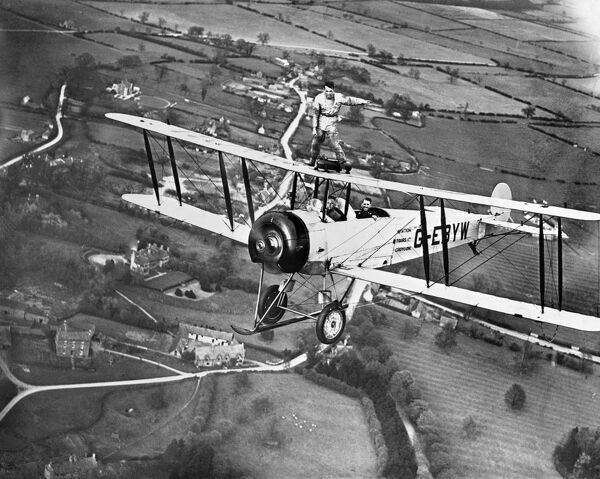Wing walking without a harness on an Aviation Tours Ltd Avro 504K. May 1932. From a copy negative. Aerofilms Collection (see Links)