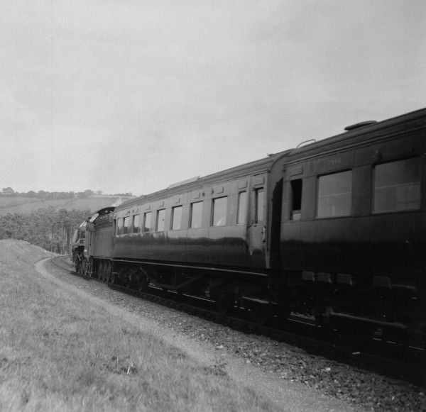 A Southern Railway 4-6-0 locomotive approaching a curve, hauling the carriages filled with passengers travelling between London and Devon