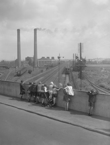 Children on Durnsford Road Bridge watching a three-car suburban electric train of the Southern Railway pass underneath