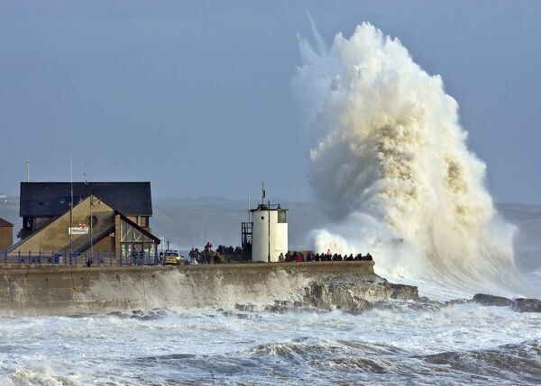 Huge wave crashing in Porthcawl harbour, the lifeboat station to the left of the image
