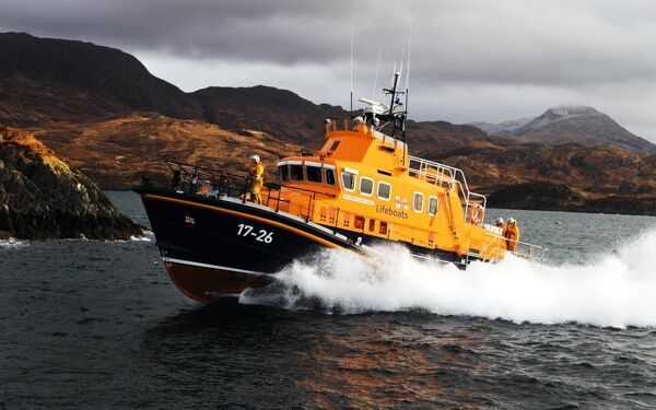 Mallaig severn class lifeboat Henry Alston Hewat 17-26. Lifeboat in the distance moving from right to left, hills and cliffs behind