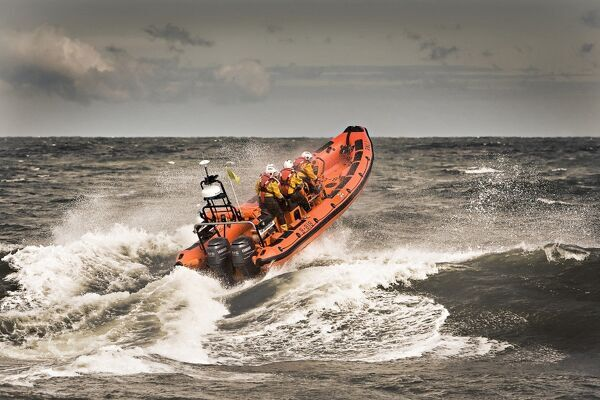 Sheringham Atlantic 85 inshore lifeboat The oddfellows B-818. Lifeboat is heading away from the camera over a breaking wave, bow high out of the water and four crew on board
