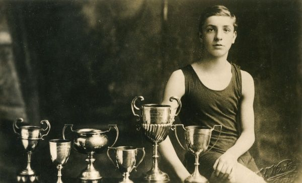 A 14-year-old swimming champion poses with the six trophies he has won. (1 of 2) Date: 1924