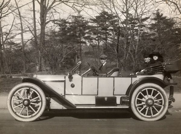 Harry G Potter. Autos, Old Styles. - 1913 American Tourist automobile with driver and two passengers in a wooded area