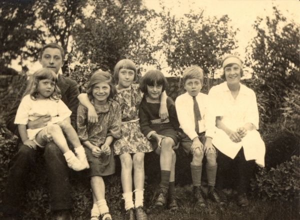 A group of boys and girls sit together in a countryside setting during the 1920s, as evidenced by the bobbed hair of some of the girls and short dresses