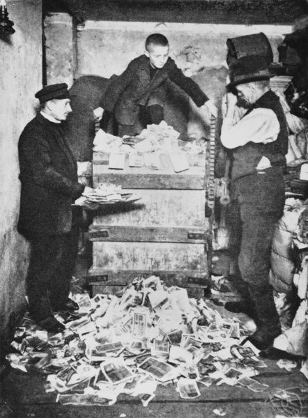 A boy and men with a pile of useless Deutsch mark banknotes as hyperinflation hits Germany in 1923