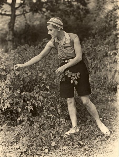 A picture of a lady in a rather chic ensemble of shorts, blouse, sandals and beanie hat, in garden looking as if she is perhaps picking blackberries or dealing with a few weeds