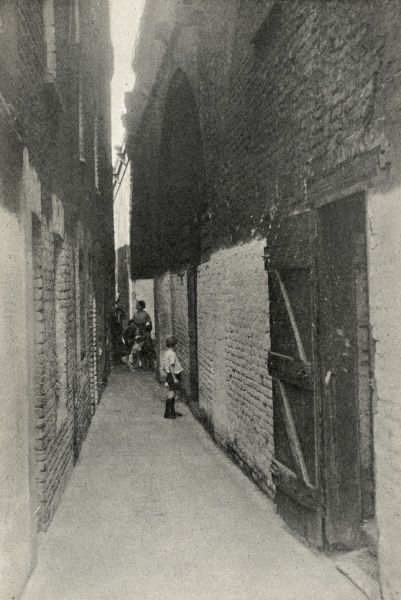 Women and children in a passageway between blocks of poor housing in the Shadwell district of Stepney in London's East End. Date: circa 1936