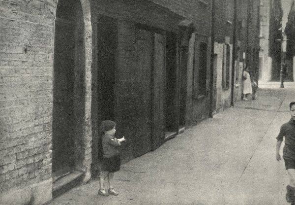 A small child stands outside a row of dilapidated houses on a poor street in Stepney in the East End of London. Date: circa 1936